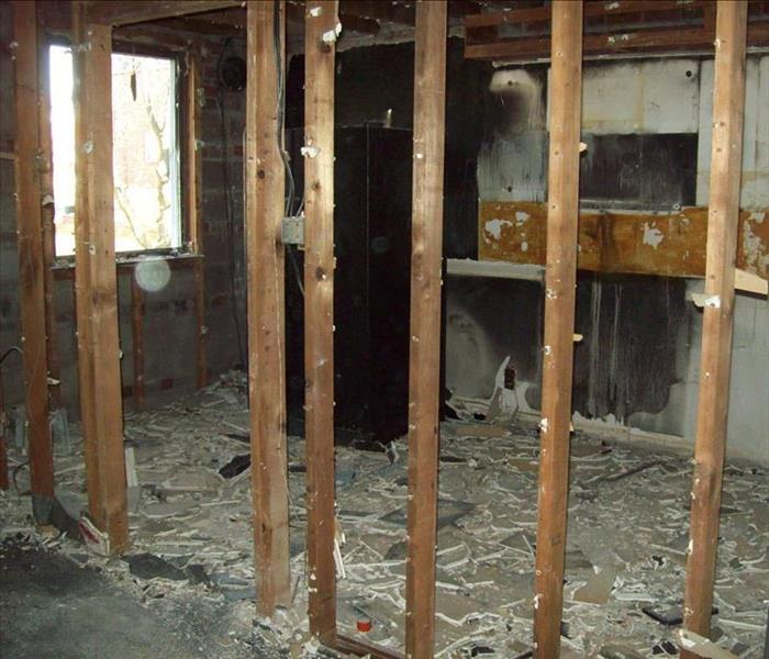 The kitchen is shown with severe fire damage, no walls, and debris everywhere.