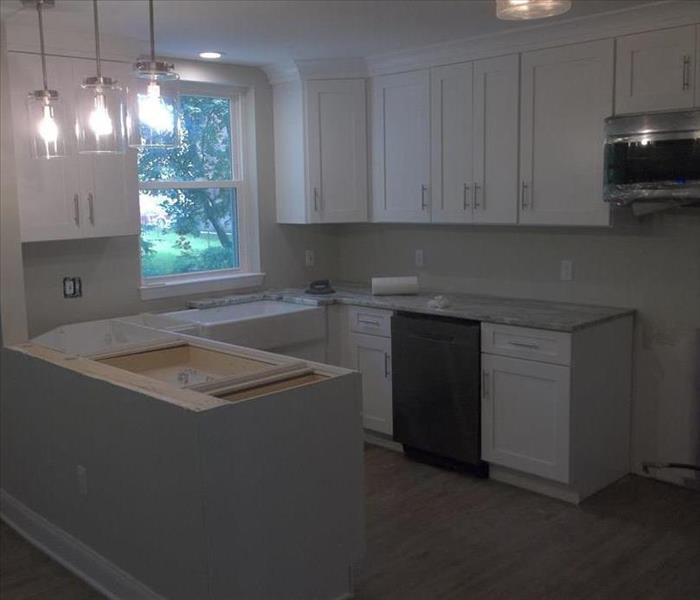 The kitchen is shown toward the end of repairs, with a new window, new appliances, and new counter tops.