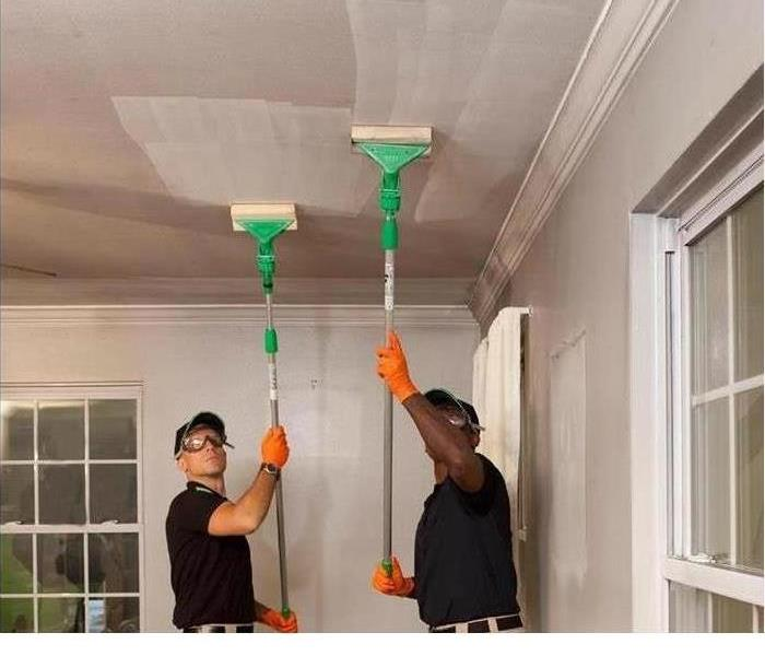 SERVPRO technicians cleaning soot off of a ceiling using sponges
