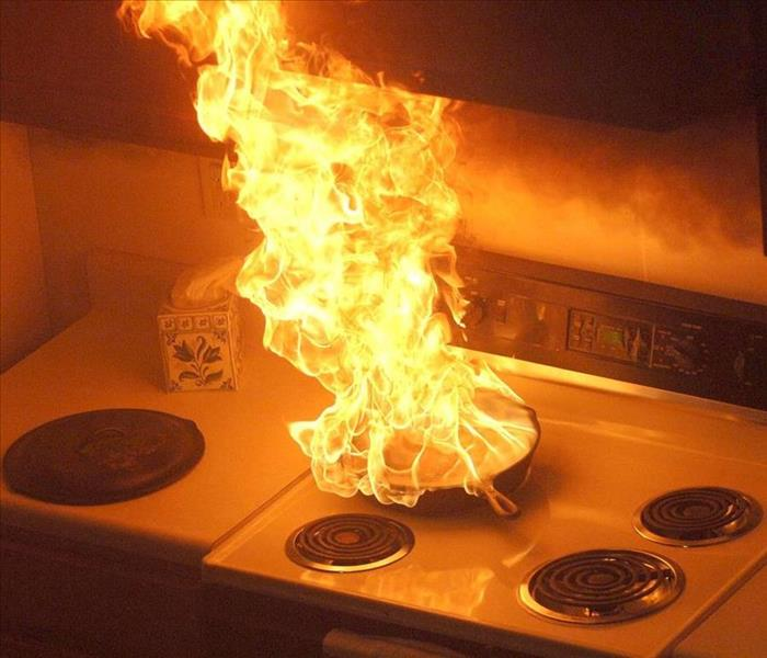 a pan catching fire on a stove